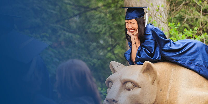 Penn State student posing for a graduation photo on the Nittany Lion Shrine.