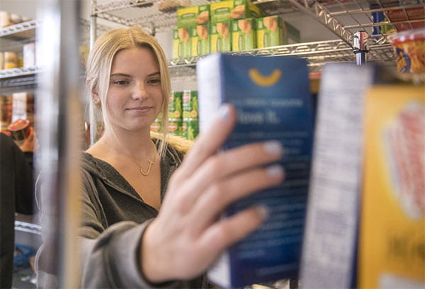 Student stacking items on pantry shelf.