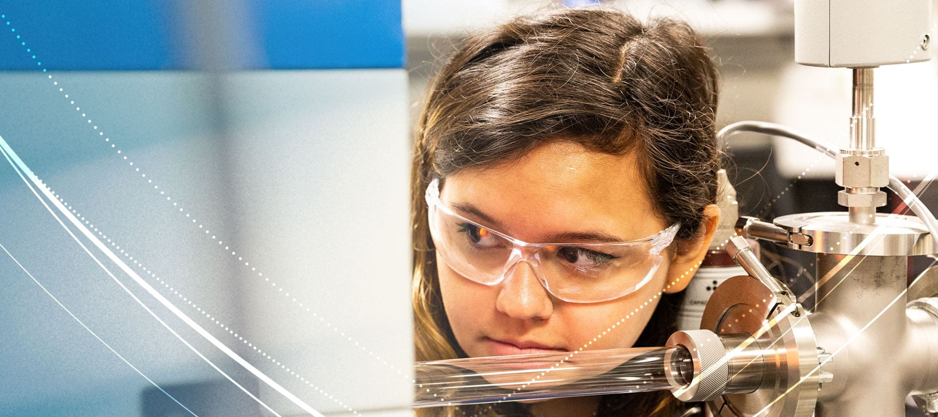 Penn State student, Ana De La Fuente Duran looks through a heating element in a piece of lab equipment.