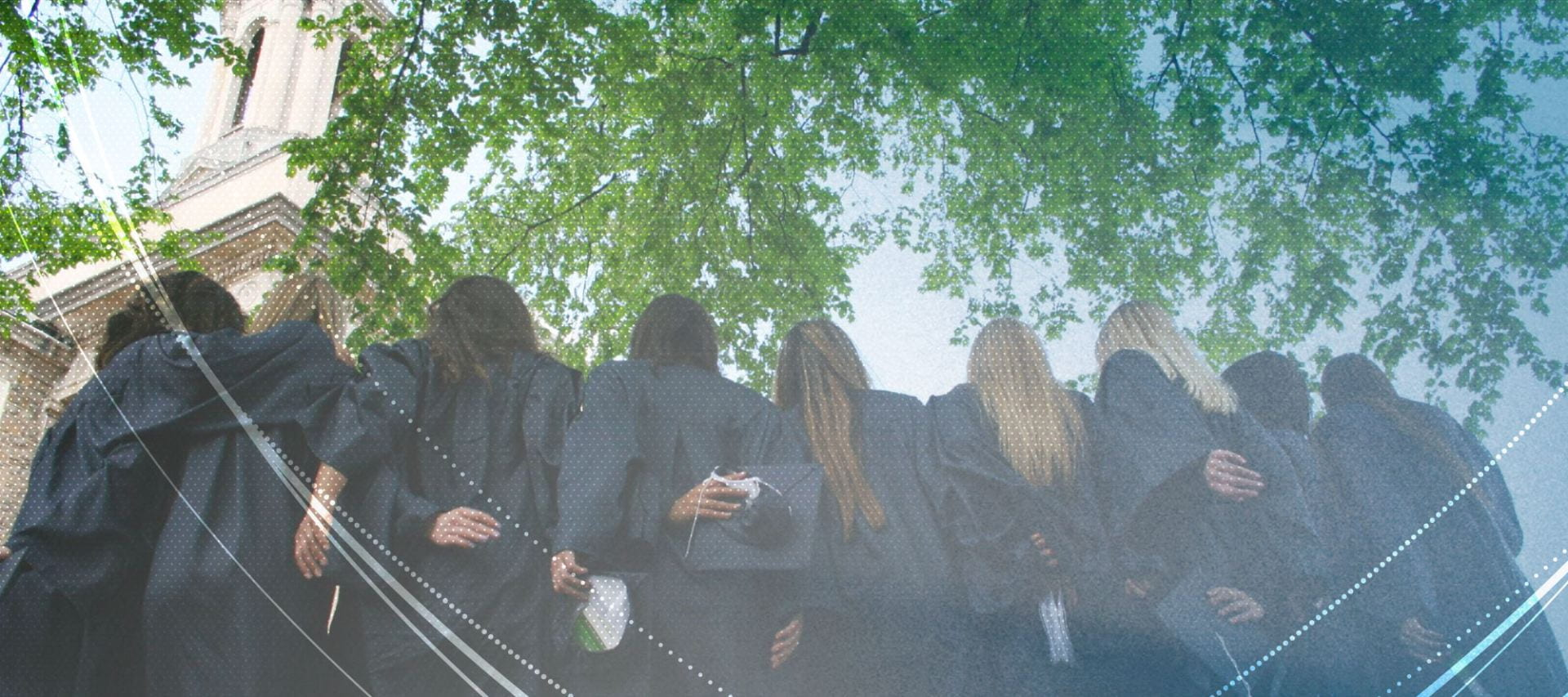 Penn State women graduates in graduation gowns in front of Old Main.